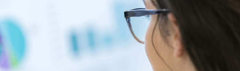 Female with glasses looking at computer screen